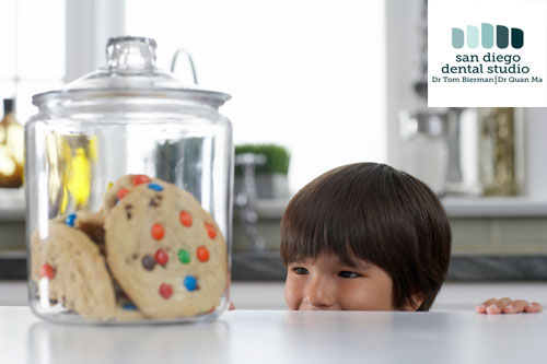 A boy looking at a jar full of cookies.